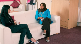 Two women discussing financial abuse on a sofa