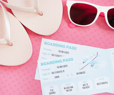Plane tickets to San Francisco, a pair of sunglasses and a pair of flip flops on a pink background.