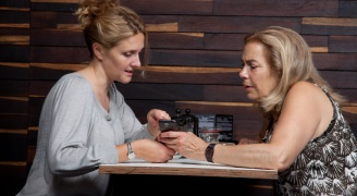 Two women sitting at a table looking at a mobile phone screen