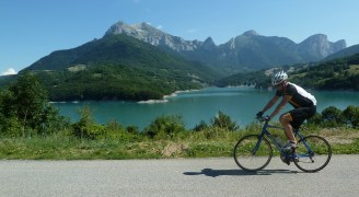 A man cycling with a scenic landscape of mountains and blue water in the background