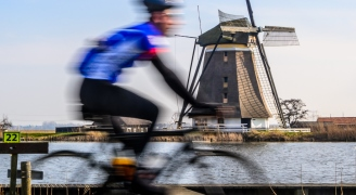 A male cyclist riding past a large windmill and open water.