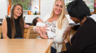 Three women and baby sit at a table