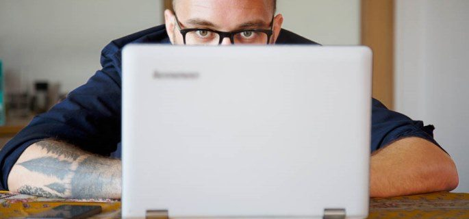 A close up of a man using a laptop
