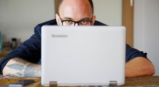 A close-up of a man on a laptop
